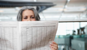 woman-reading-newspaper-airport-628x363